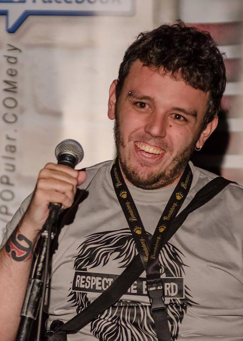 Richie pictured from the shoulders up in a grey shirt. He has short, dark brown hair and is holding a microphone. The background is of a comedy club and features a wall with vinyl records stuck to it.