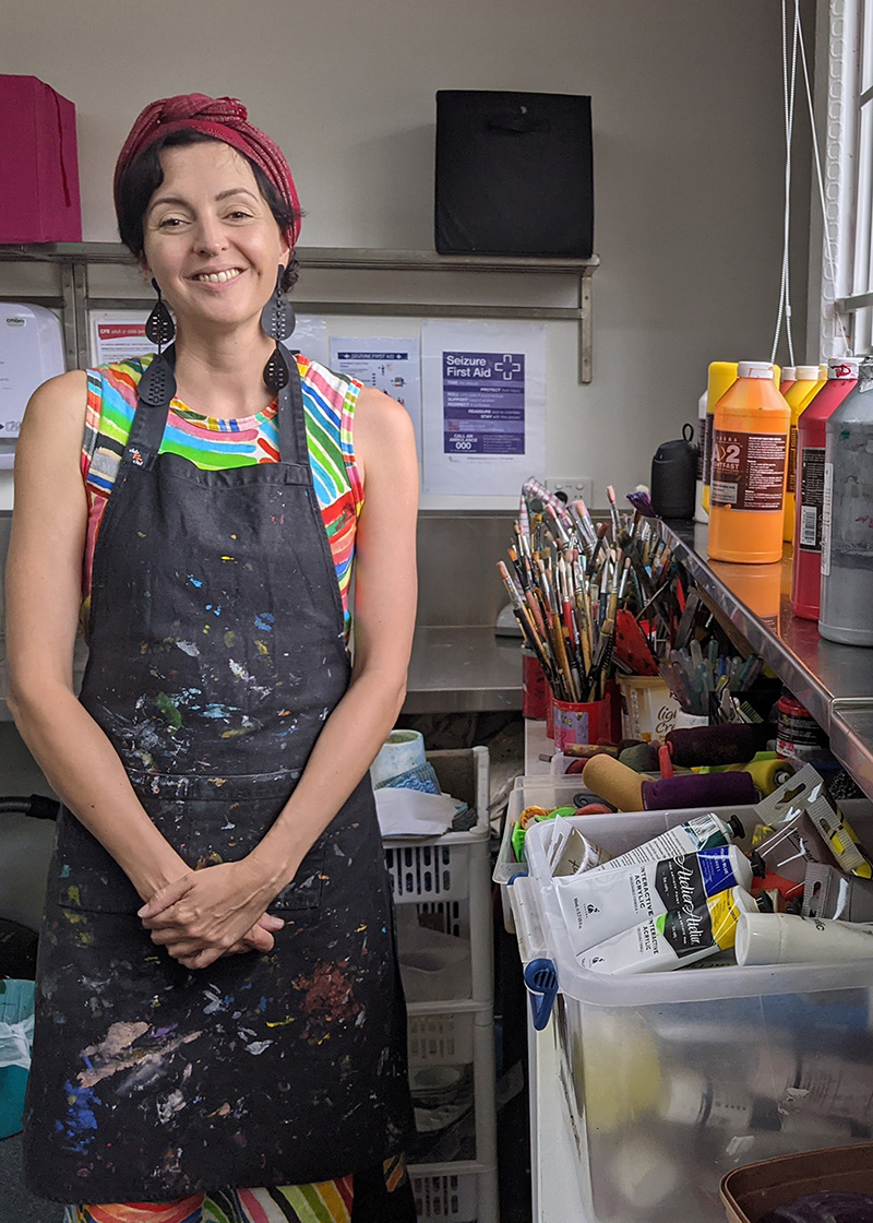 Alice Gittins standing in Access Arts studio. Alice is wearing a green shirt with an apron with lots of paint on it.